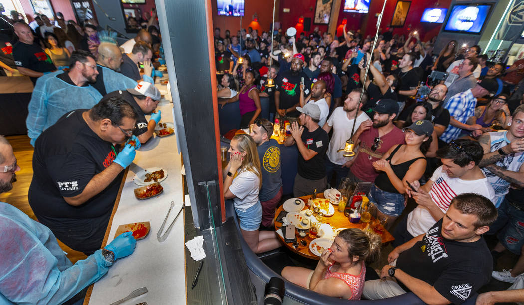 Competitors eat as supporters watch and cheer them on as PT's Ranch hosts a $4,000 wing-eating ...