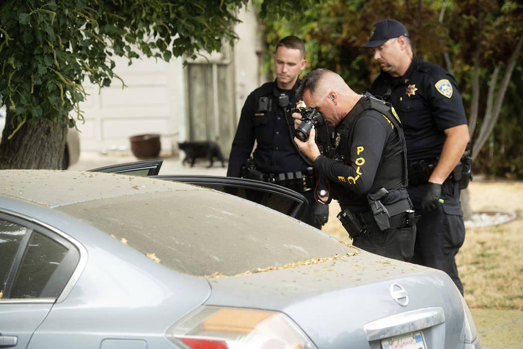 A police officer photographs a car outside the family home of Gilroy Garlic Festival gunman San ...