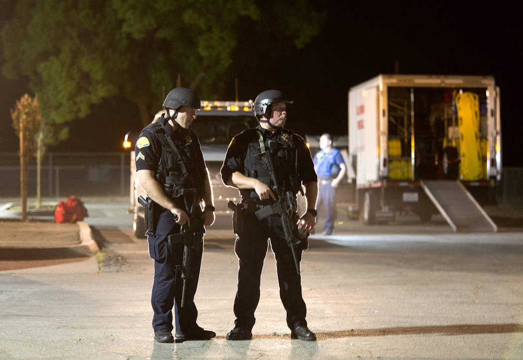 Police officers dressed in SWAT gear stand guard at the first aid center at Gilroy High School ...