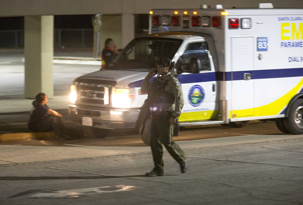 A police officer dressed in SWAT gear walks through the first aid center at Gilroy High School ...