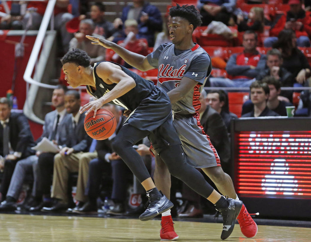 Colorado guard Shane Gatling, left, drives around Utah forward Donnie Tillman, right, during th ...