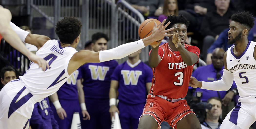 Washington's Matisse Thybulle (4) stretches across to try to stop a pass from Utah's Donnie Til ...