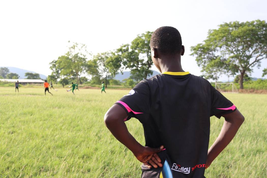 A young man waits to sub into a local town soccer match from the Vima Orphanage in Tsibu-Bethel ...
