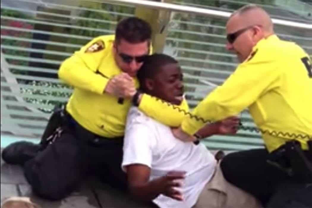 A screenshot from a 2013 video shows 2 Las Vegas police officers apprehending a man on the Las ...