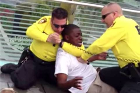 A screenshot from a 2013 video shows two Las Vegas police officers apprehending a man on the La ...