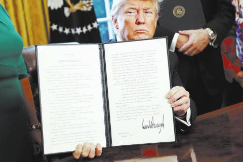 President Donald Trump holds up an executive order after his signing the order in the Oval Offi ...