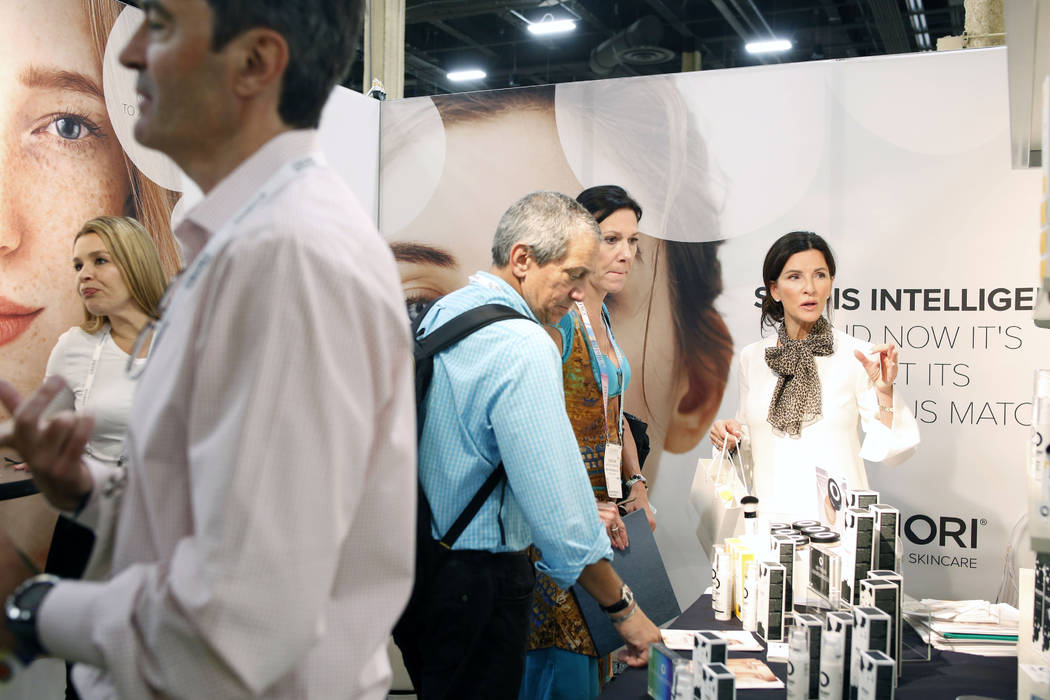 Individuals inquire about Priori Skincare products at Cosmoprof North America at the Mandalay B ...
