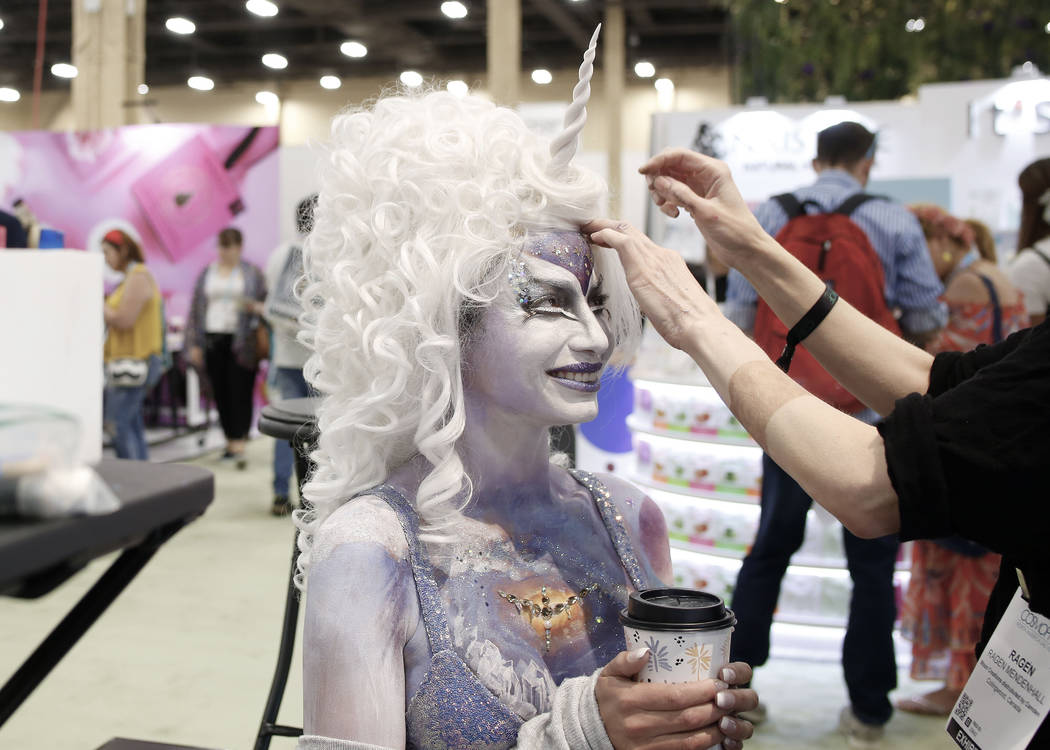 Body art model Charlei Garcia receives final touches at the Moon Creations booth at Cosmoprof N ...