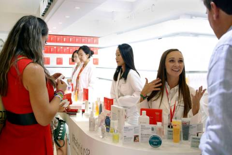 Individuals inquire about Vitabrid C12 products during Cosmoprof North America at the Mandalay ...