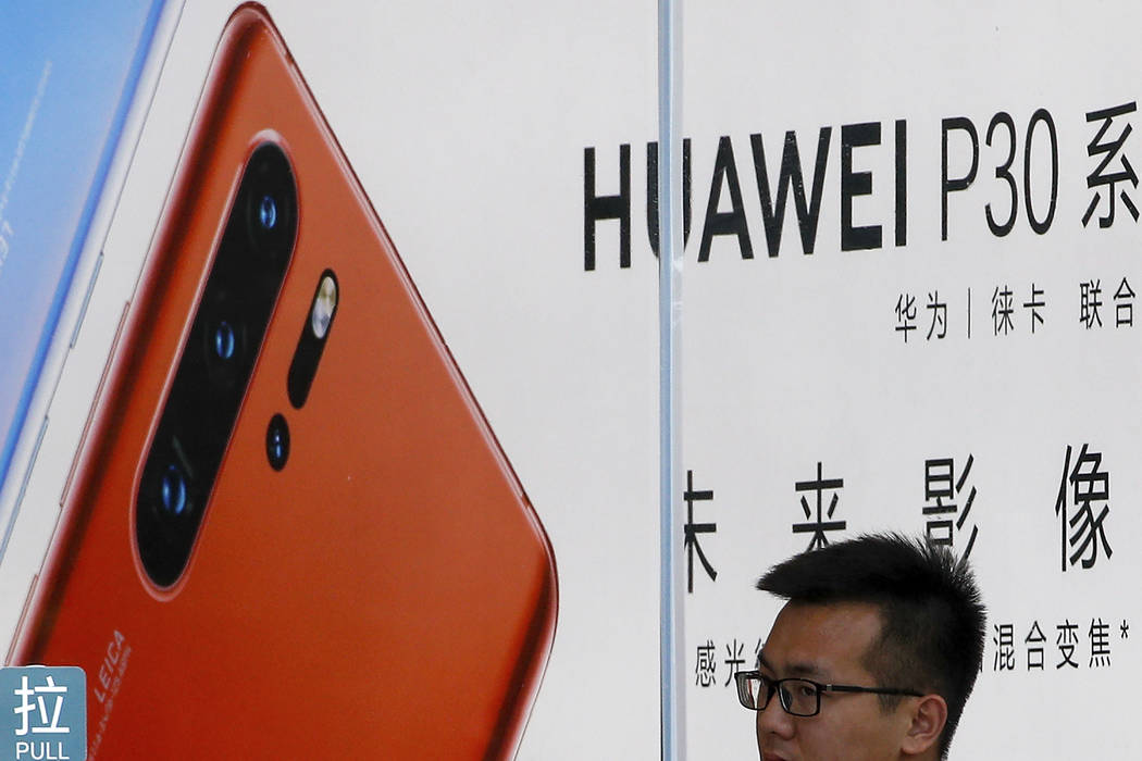A staffer looks out from a Huawei retail store in Beijing, Tuesday, July 30, 2019. Huawei's glo ...