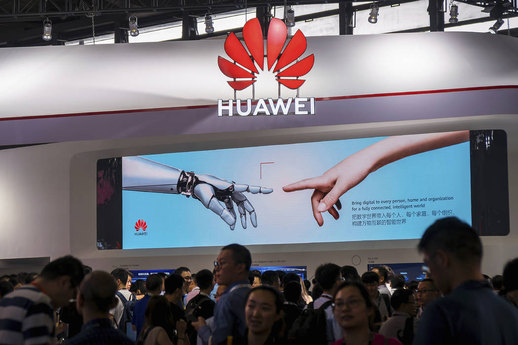 In a June 26, 2019, photo, visitors tour the Huawei pavilion at the Mobile World Congress in Sh ...