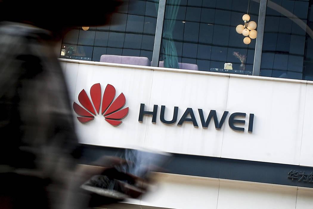 A woman walks by a Huawei retail store in Beijing, Tuesday, July 30, 2019. Huawei's global sale ...