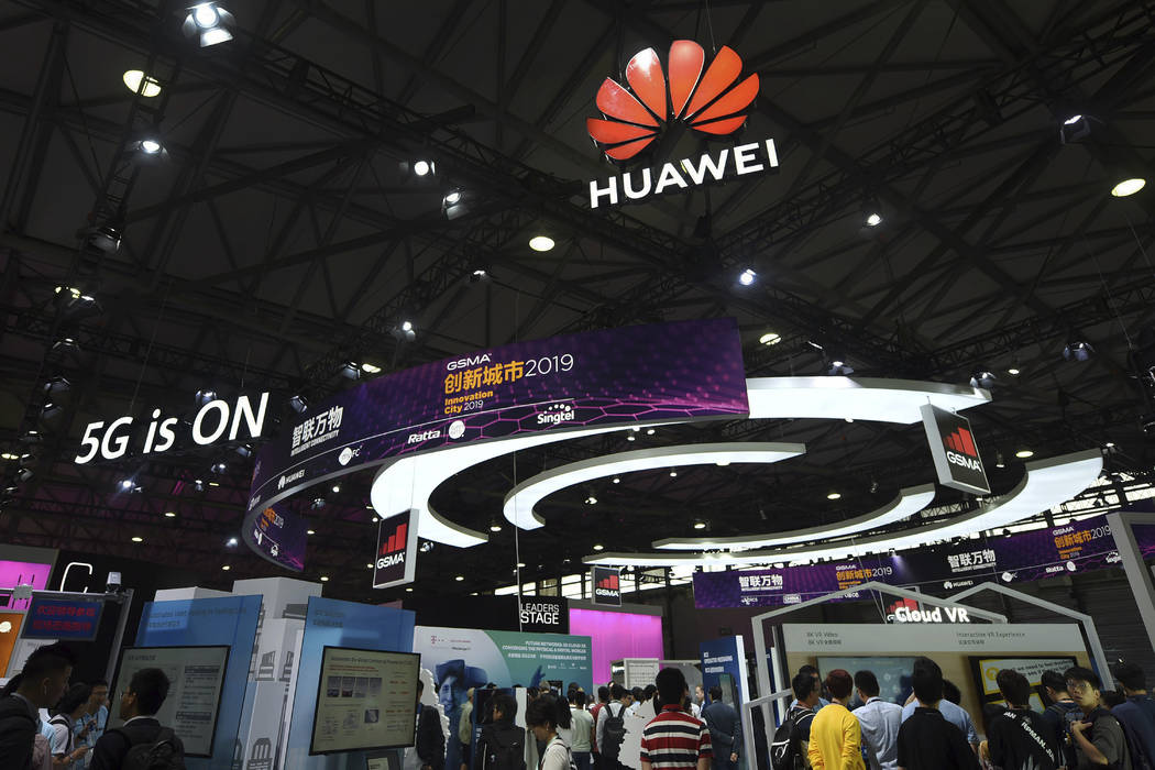 In this June 27, 2019, photo, visitors tour the Huawei pavilion at the Mobile World Congress in ...