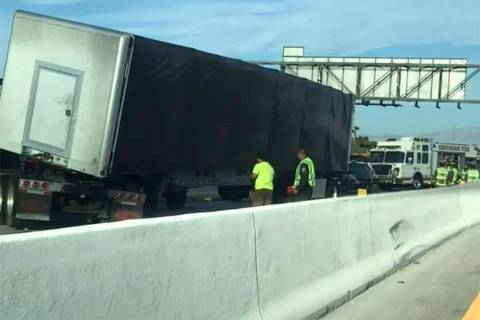 Workers inspect a semi involved in a crash at Interstate 215 and Gibson Road on Tuesday, July 3 ...