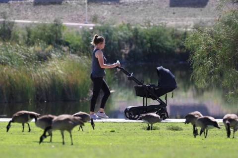 A woman pushes a baby in a stroller as she walks at Cornerstone Park during a hot morning on Mo ...