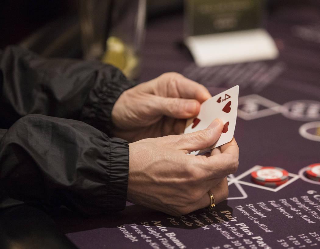 A gambler looks at her cards at a blackjack table at SLS Las Vegas on Thursday, May, 30, 2019, ...