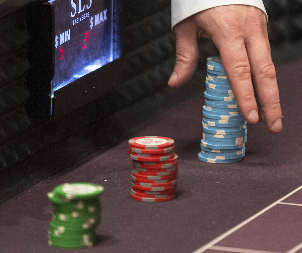 A dealer moves a stack of chips on the craps table at SLS Las Vegas on Thursday, May, 30, 2019, ...