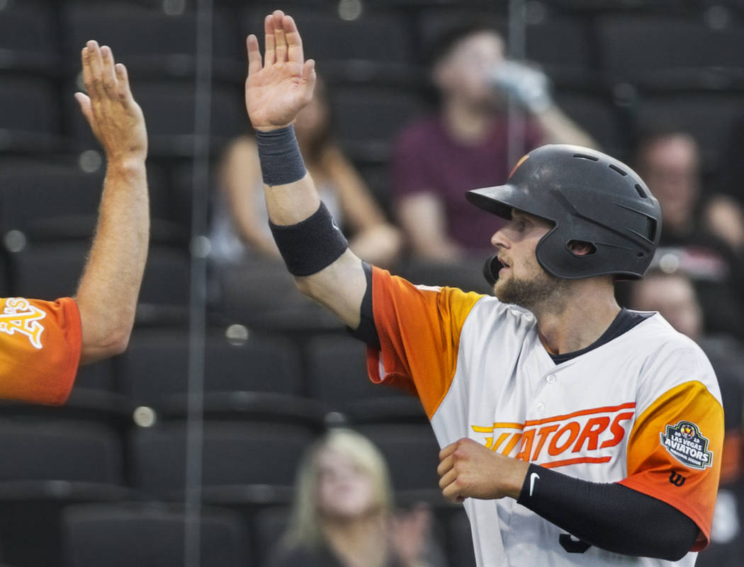 Las Vegas Aviators first baseman Seth Brown, right, high fives his teammates after scoring in t ...