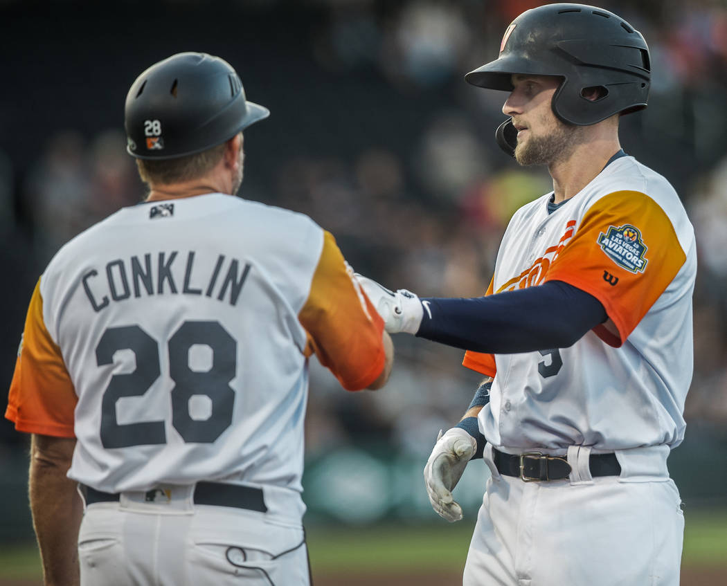 Las Vegas Aviators first baseman Seth Brown (9) high fives first base coach Craig Conklin (28) ...