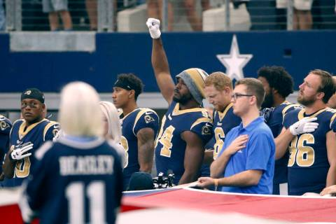 Then-Los Angeles Rams linebacker Robert Quinn (94) raises his fist during the playing of the na ...