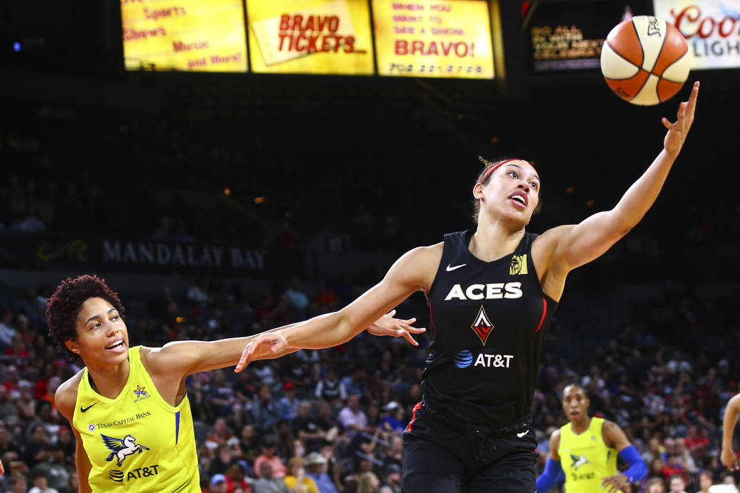 Las Vegas Aces' Dearica Hamby, right, gets a rebound in front of Dallas Wings' Isabelle Harriso ...