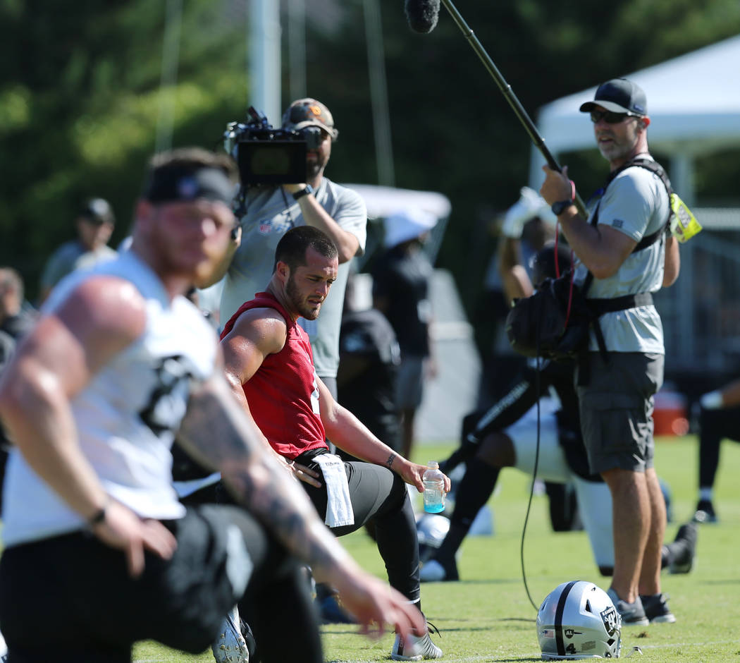 The HBO Hard Knocks crew film Oakland Raiders quarterback Derek Carr (4) as he stretches during ...