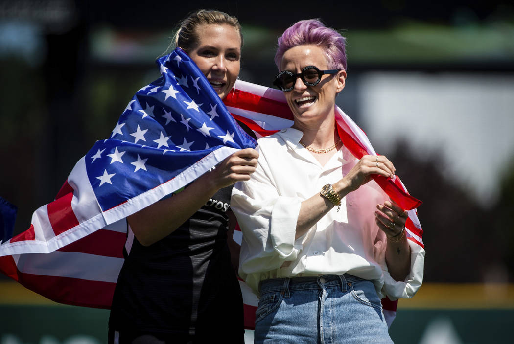 Reign FC midfielder Allie Long, left, and forward Megan Rapinoe, right, wrap themselves in an A ...