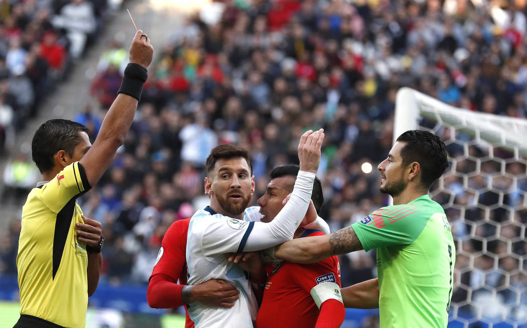 Argentina's Lionel Messi, center left, and Chile's Gary Medel, center right, scuffle as referee ...