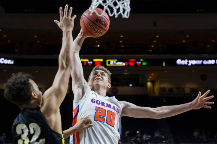 Bishop Gorman junior guard Noah Taitz (20) drives over Clark senior forward Ian Alexander (32) ...