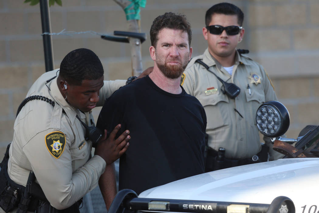 A man is escorted by Las Vegas police officers at the Smith's Marketplace, at 9710 West Skye Ca ...