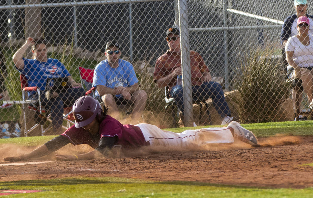 Desert Oasis infielder Andrew Martinez (2) slides into home base as the winning run during t ...