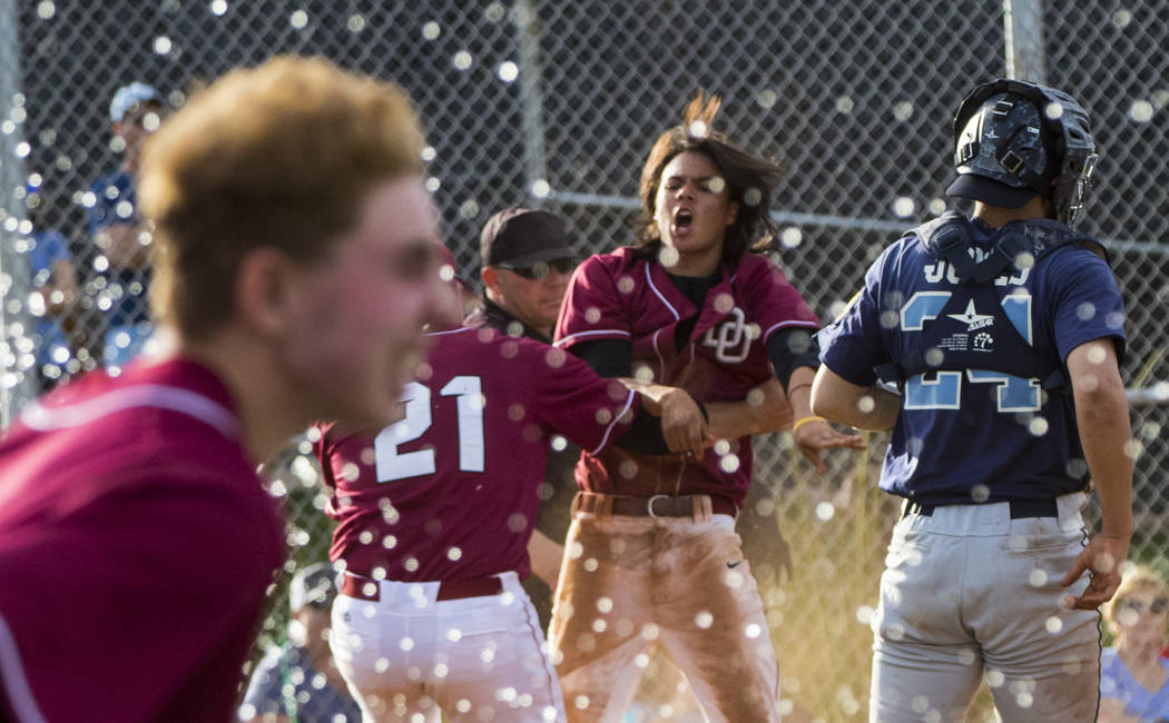 The Desert Oasis High School baseball team celebrates their win after the championship game ...