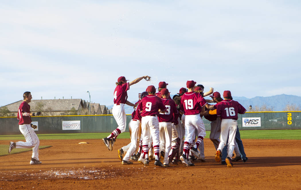 The Desert Oasis High School baseball team celebrates their win against Centennial High Scho ...