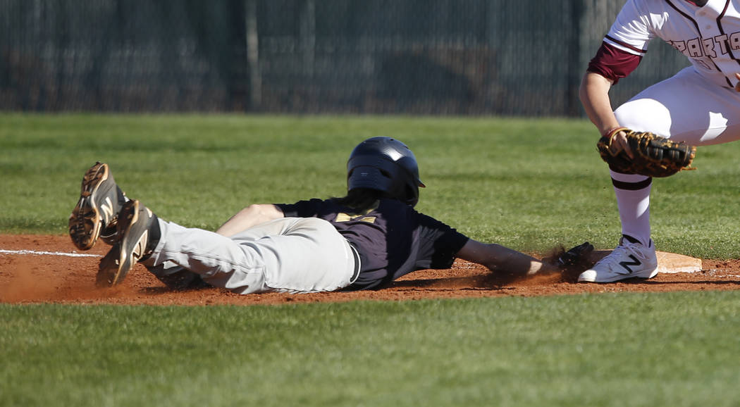 Faith Lutheran's Paulshawn Pasqualotto (2) dives for first base during a high school b ...