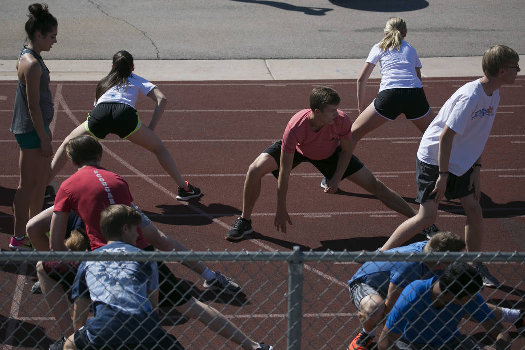 Garett Furlong, center, warms up with teammates during a track and field practice at Coronad ...