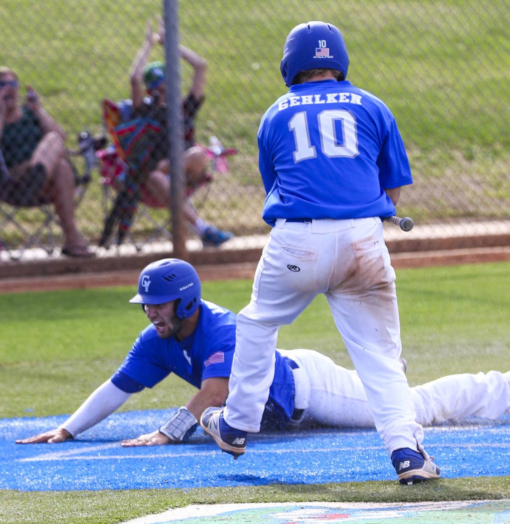 Green Valley shortstop A.J. Amelburu (11) slides into home plate in the second inning during ...