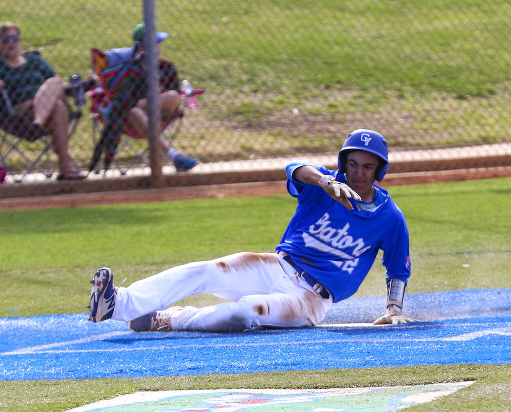 Green Valley outfielder Matt Uran (22) slides into home plate in the second inning during a ...