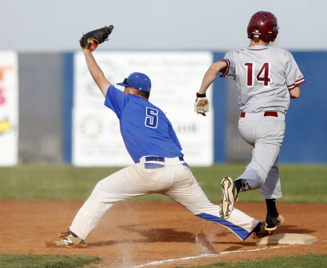 Desert Oasis's Jake Schmidt (14) is out at first base after a catch by Sierra Vista&#8 ...