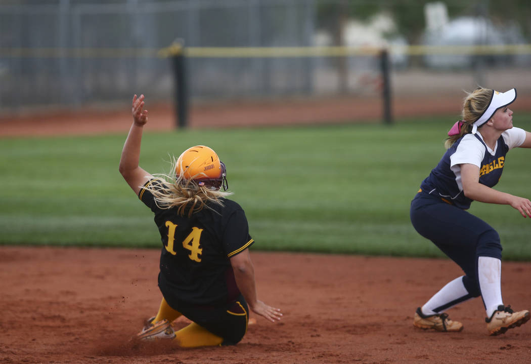 Pahrump's Jordan Egan (14) slides into second base against Boulder City's Micayl ...