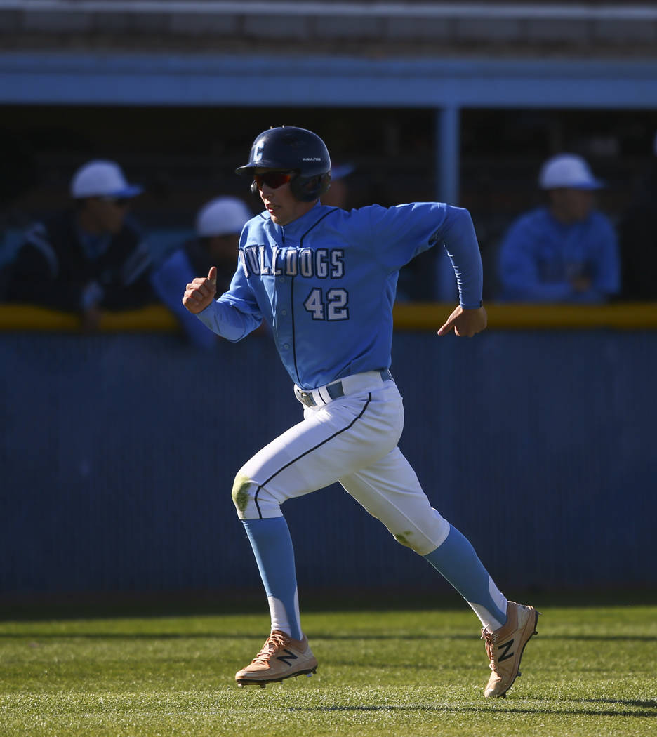 Centennial's Jake Rogers (42) heads for home base to score a run against Cimarron-Memo ...