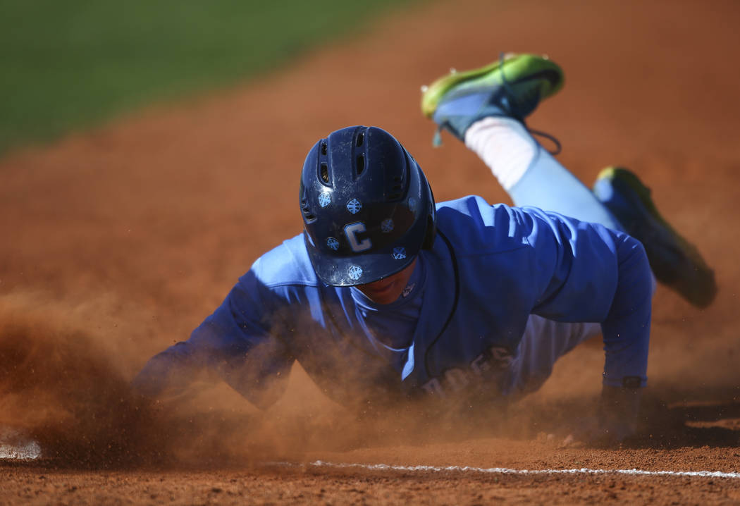 Centennial's Kian Wilbur (4) slides back to first base to stay safe during a baseball ...