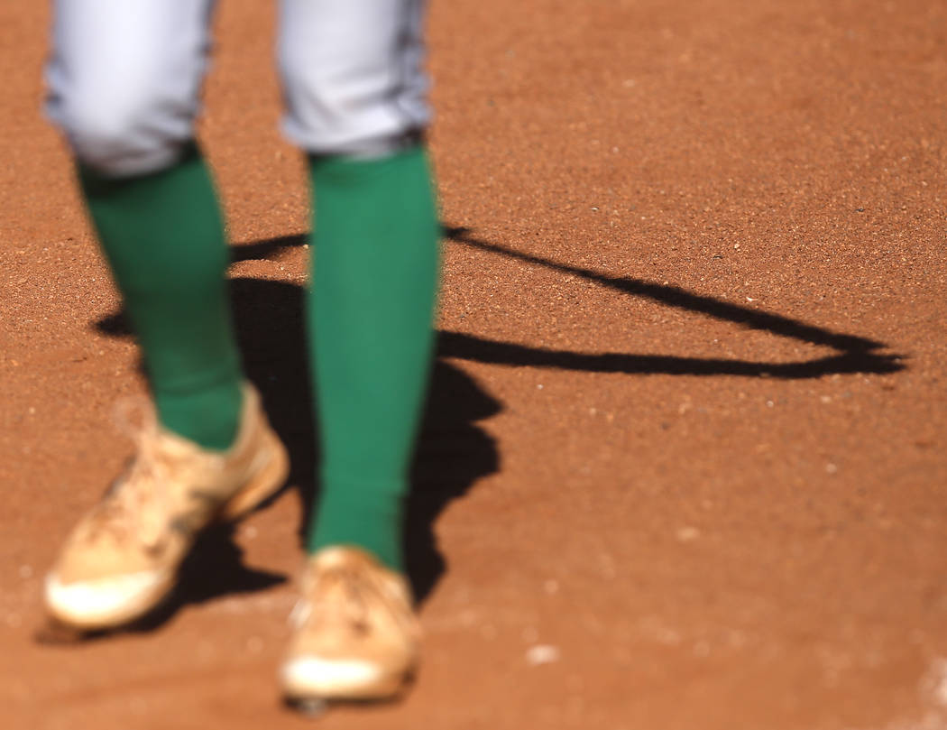 The shadow of a Palo Verde athlete is seen as she stretches before her turn at bat during th ...