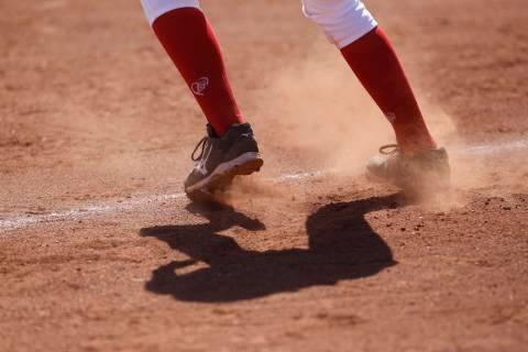 Dust flies as a player leads off third base during a high school softball game at Coronado H ...