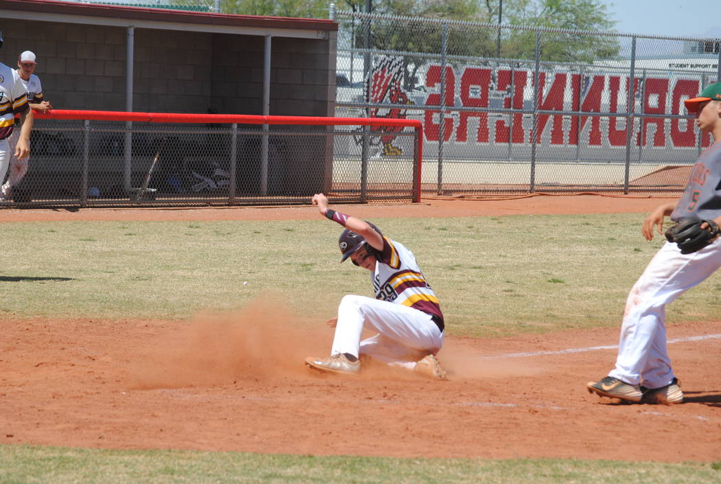 A Pahrump Valley player slides across the plate to score a run on Wednesday. The Trojans bea ...