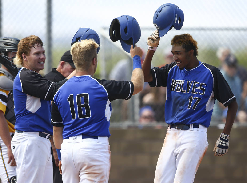 Basic's Garrett Giles (17) celebrates his home run with Jack Wold, left, and Trace Eva ...