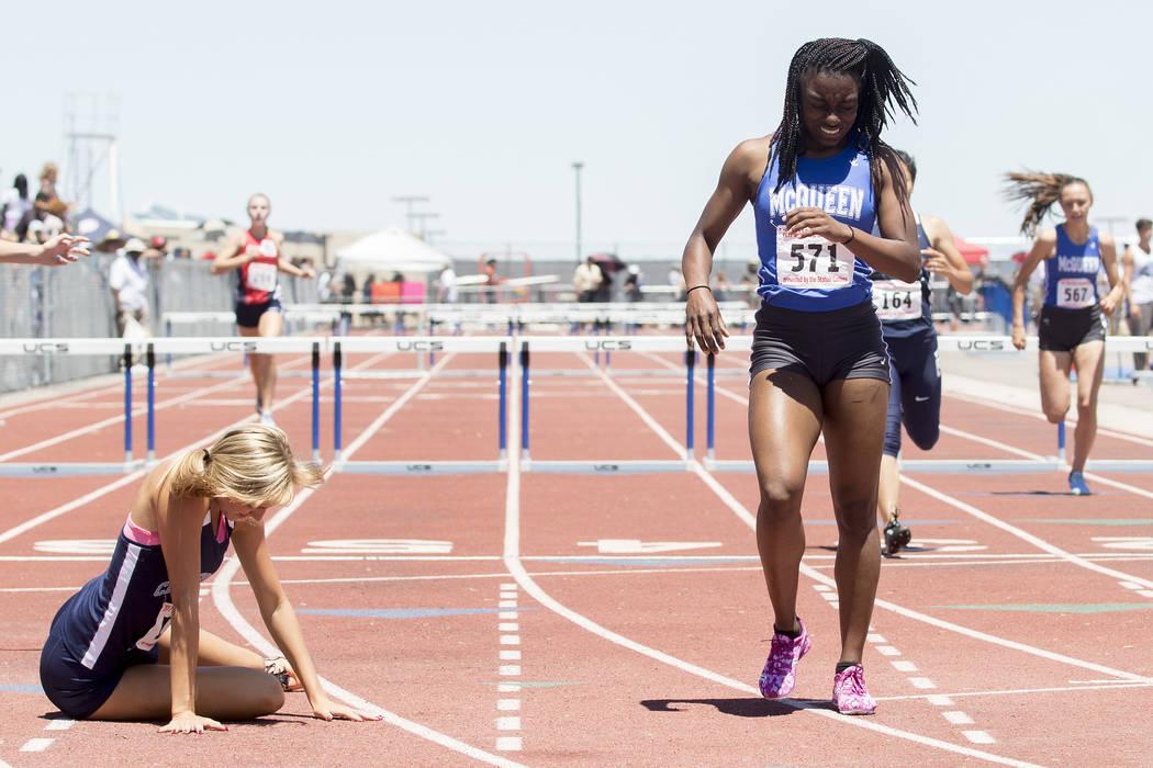 Centennial senior Talie Bonds falls to the ground next to McQueen junior Destiny Tolliver af ...