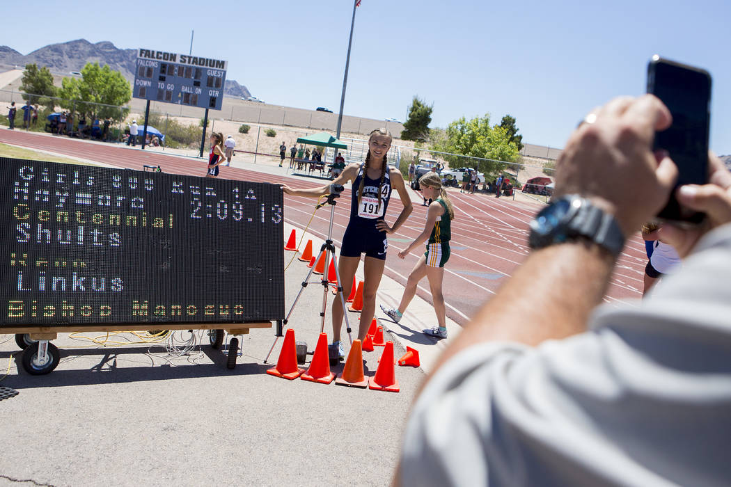 Centennial senior Karina Haymore takes a picture with her time after the girls 800-meeter ru ...