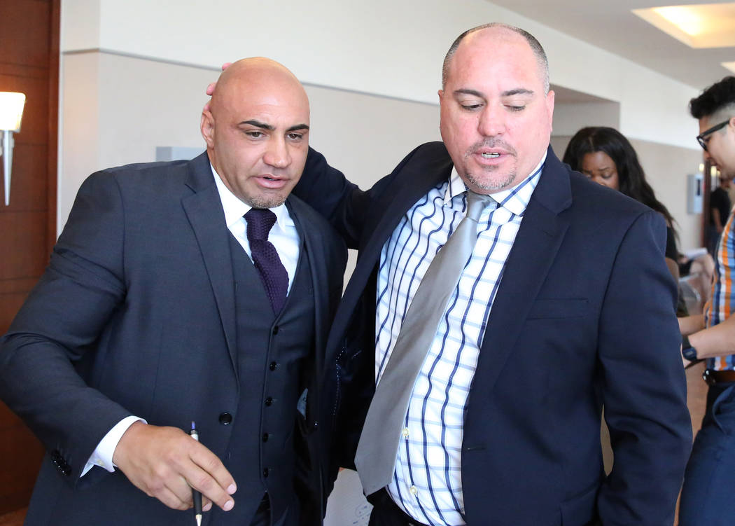 Kenny Sanchez, Bishop Gorman High School football head coach, left, leaves the courtroom wit ...