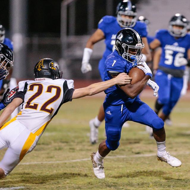 Pahrump Valley senior Drew Walker (22) reaches out for Desert Pines senior Isaiah Morris (7) ...