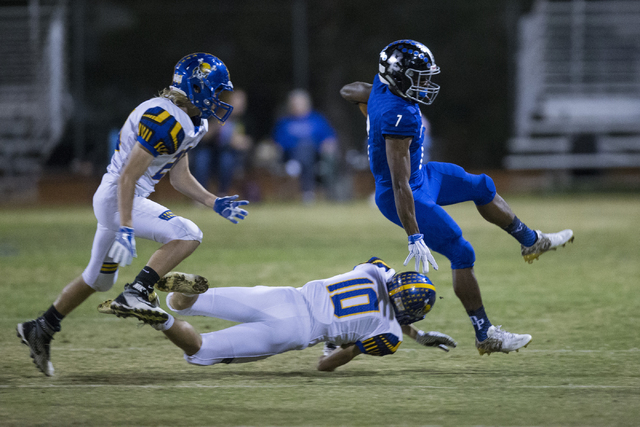 Desert Pines running back Isaiah Morris (7) leaps over a tackle attempt by Moapa Valley&#821 ...